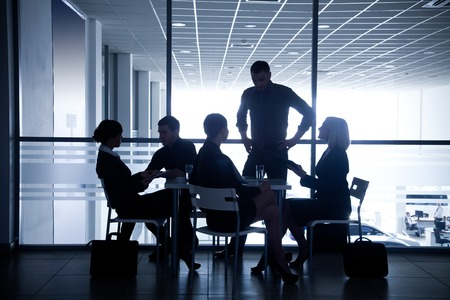 Several silhouettes of businesspeople interacting  background business centre Stock Photo - 27439682