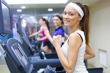 groupe de jeunes gens courir sur le tapis roulant en salle de gym