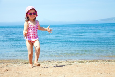 happy little girl at the seaside in the summer time photo