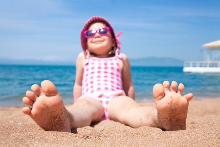 petite fille couchée sur une plage de sable et se faire bronzer au soleil Banque d'images