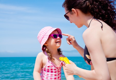 Mom anoints protective cream face a little girl on the beach Stock Photo - 27439776