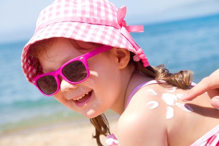 Mom anoints protective cream back a little girl on the beach photo