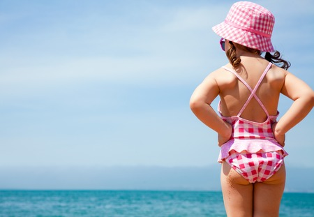 little girl in a swimming suit looks at the sea Reklamní fotografie