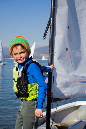 little boy on a small yacht sail photo