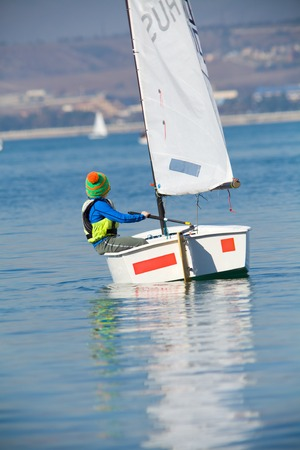 little boy on a small yacht sail Stock Photo