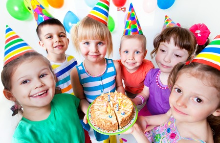 party food: group of children at birthday party with cake