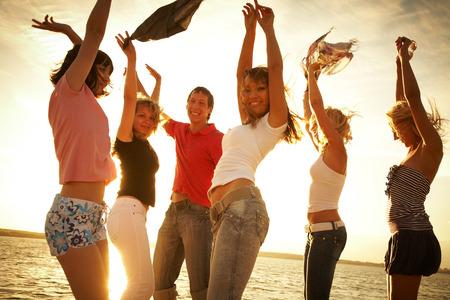 vacaciones playa: Grupo de j�venes felices bailando en la playa en el atardecer de verano hermosa