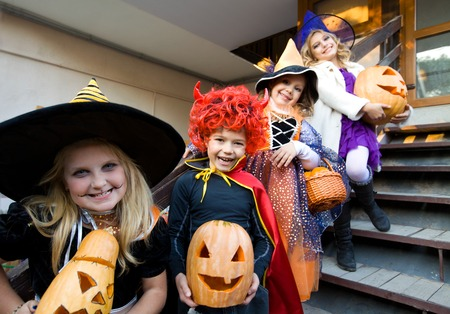 children in halloween costumes with pumpkin walk in guests photo