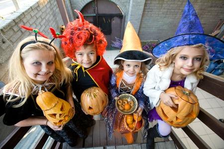 children in halloween costumes with pumpkin walk in guests