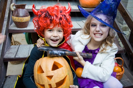children in halloween costumes with pumpkin fooled on holiday photo