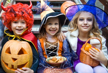 treat: children in halloween costumes with pumpkin fooled on holiday Stock Photo