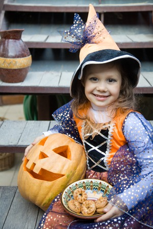 girl in a witch costume with halloween pumpkin on holiday photo