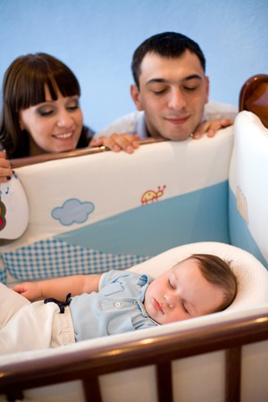 admires: happy young family admires a sleeping newborn son