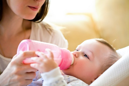 love mom: happy mother feeds the baby bottle
