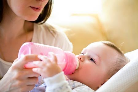 mleko: szczęśliwa matka karmi dziecko butelką