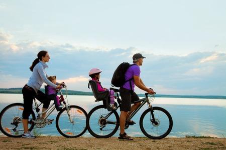 pareja saludable: Familia joven con dos niños ir a dar un paseo en bicicleta por la playa al atardecer de fondo