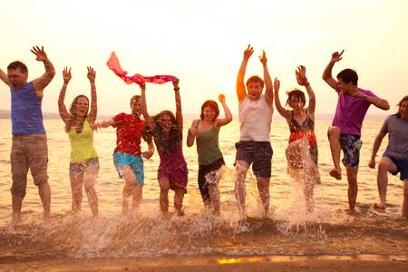 personas saltando: grupo de jóvenes saltando feliz en la playa en la hermosa puesta de sol del verano Foto de archivo
