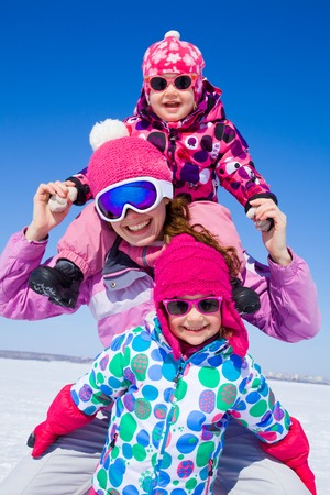 Portrait of smiling woman with two cute little girls in wintertime photo