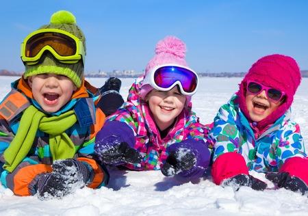 kinder spielen: Gruppe von spielenden Kindern auf Schnee im Winter