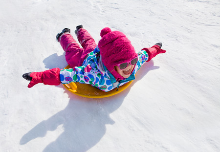 kids activities: little girl riding on snow slides in winter time Stock Photo