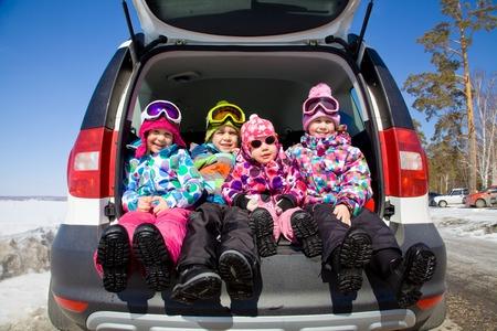 groep van kinderen in de winter kleren zitten in de kofferbak van een auto Stockfoto