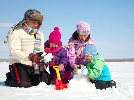 cold season: Happy couple with two children making big snowman