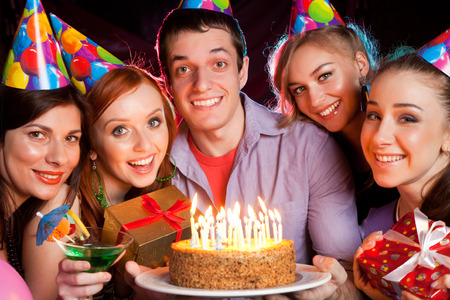 group of young people on birthday party with cake