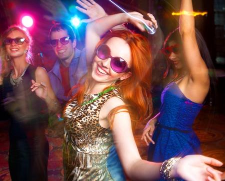 gente bailando: Grupo de jóvenes que se divierten bailando en la fiesta.
