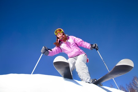 young beautiful skier rides a ski resort on a background of blue sky photo
