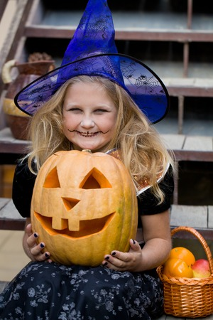8   9 years: girl in a witch costume with halloween pumpkin on holiday