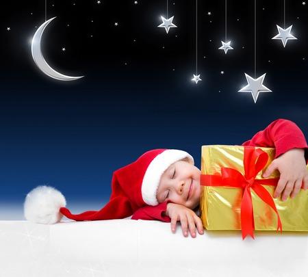 Enfant de Noël dort avec un cadeau sur fond de conte de fées nuit Banque d'images