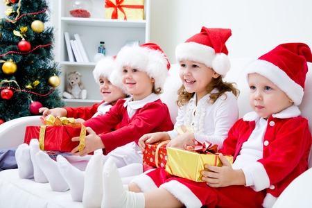 Group of four children in Christmas hat with presents on couch