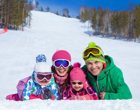 snow ski: happy family in winter clothes lie on the snow at ski resort