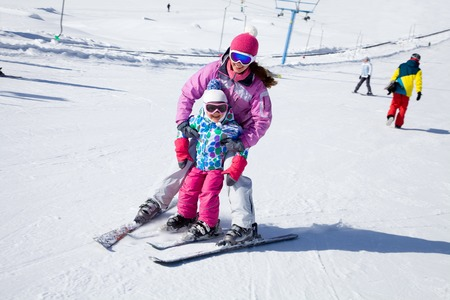 Female instructors teach a child skiing on winter resort