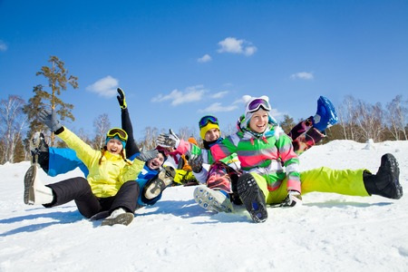 group of funny friends slide downhill together on mountain holiday Stockfoto