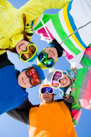 Group of young people in ski glasses on ski holiday in mountains