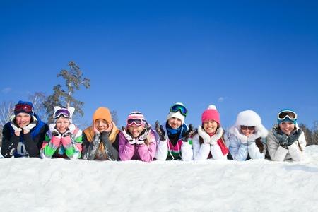 teen: Grupo de adolescentes que mienten en nieve en la estaci�n de esqu�
