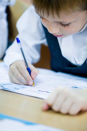 pre adolescent boys: schoolboywrites in a notebook at school Stock Photo