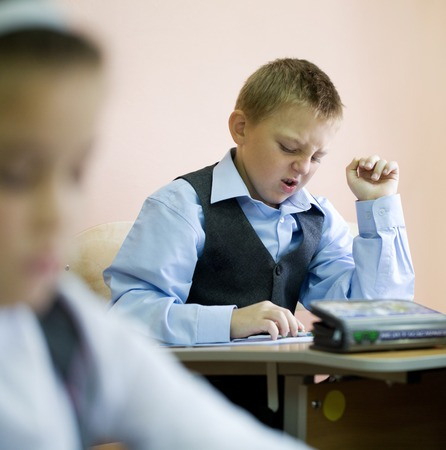 pre adolescent boys: schoolchildren sit at their desks in elementary school