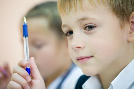 schoolboy: little schoolboy with pen in classroom