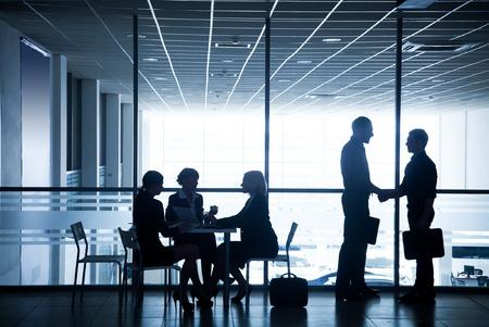 reuniones empresariales: Varias siluetas de los empresarios interactuar centro de negocios fondo Foto de archivo