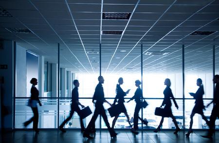 silhouettes de gens d'affaires se précipiter pour les grandes fenêtres en arrière-plan