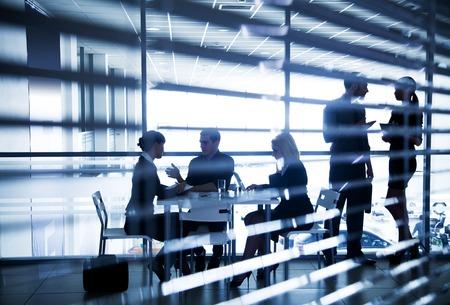 Plusieurs silhouettes de gens d'affaires qui interagissent dans le bureau
