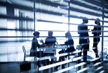 Several silhouettes of businesspeople interacting  in office Stockfoto