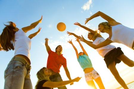 groupe de jeunes à jouer au volleyball sur la plage de coucher du soleil