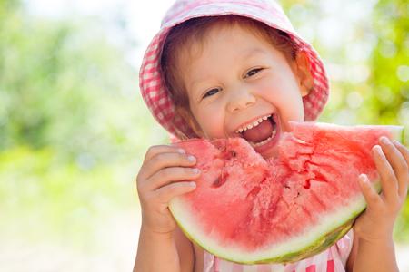 outsides: cute little girl eating watermelon in summertime