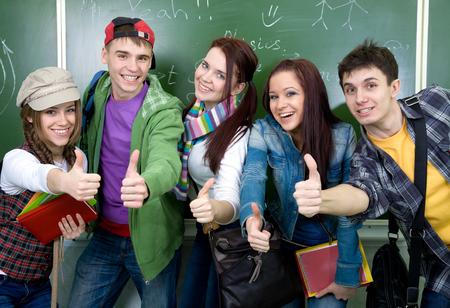 jovenes estudiantes: grupo de jóvenes estudiantes que se divierten en el fondo de la junta escolar Foto de archivo