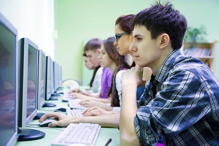 young students: grupo de jóvenes estudiantes que estudian en el aula con el ordenador