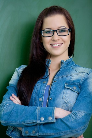 beautiful young student in glasses standing at the blackboard photo