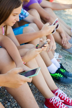 mobile internet: group of teenagers spending time together with gadgets